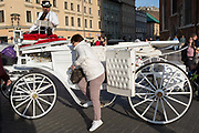 A tourist climbs down after her horse and carriage ride around Rynek Glowny market square, on 23rd September 2019, in Krakow, Malopolska, Poland.