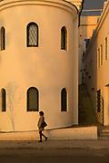Woman walking on sidewalk near Sacra Iglesia Catedral Ortodoxa de San Nicolas with windows and steps, Havana, Cuba