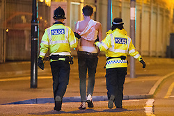 """© Licensed to London News Pictures . 22/10/2012 . Manchester , UK . A male student is lead away by two police officers . Students attend a Carnage UK pub crawl at bars in Manchester 's Deansgate Locks with a fancy dress theme of """" Pimps and Hoes """" . The event has been criticised for encouraging binge drinking , sexism and anti-social behaviour . Photo credit : Joel Goodman/LNP"""