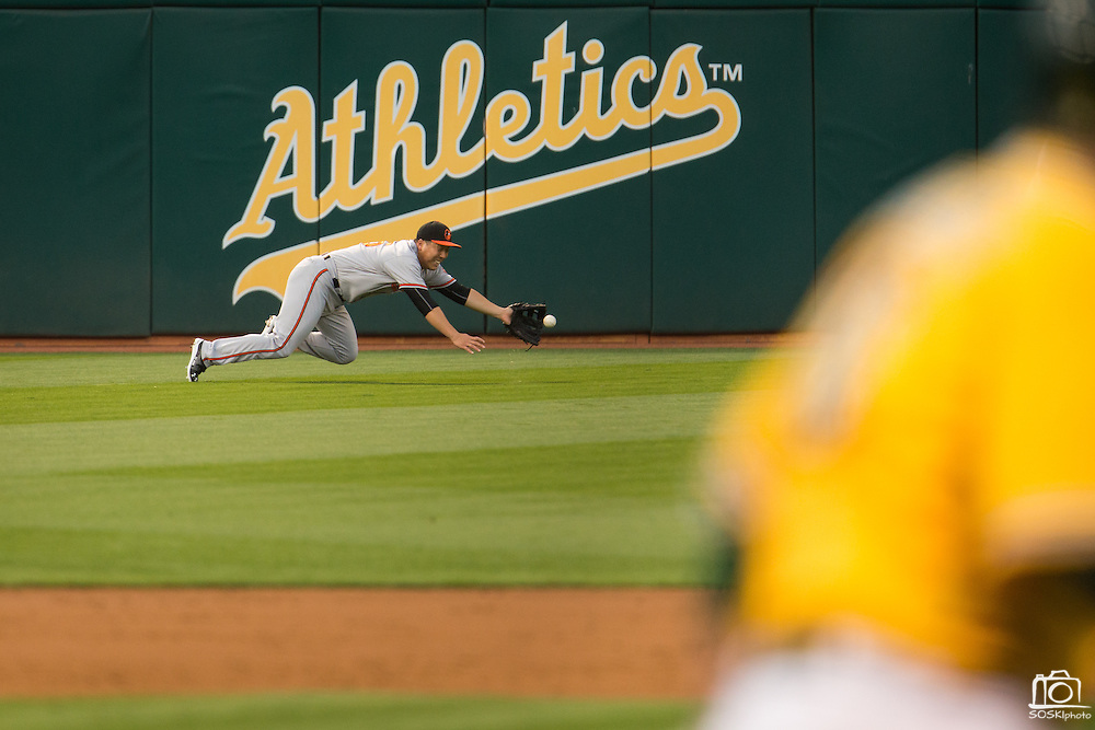 Baltimore Orioles left fielder Hyun Soo Kim (25) dives for a ball hit by Oakland Athletics designated hitter Billy Butler (16) but can't get his glove on it at Oakland Coliseum in Oakland, Calif. on August 8, 2016. (Stan Olszewski/Special to S.F. Examiner)