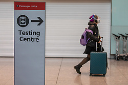 """© Licensed to London News Pictures. 24/11/2020. London, UK. A passenger walks past a Covid testing centre sign at London Heathrow Terminal 5 today. Minister for Transport Grant Shapps has announced that quarantine for air travellers will drop to 5 days from mid December if they take a private Covid test. Under the new """"test to release"""" scheme passengers who test negative after 5 days self-isolation will be able to carry on with their normal lives. Photo credit: Alex Lentati/LNP"""