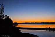 Colorful sunrise colors the water of Yellowstone Lake in Yellowstone National Park in Wyoming