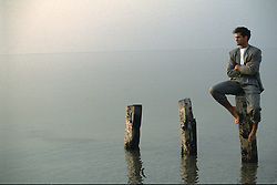 man in a suit sitting on wooden posts in a calm sea
