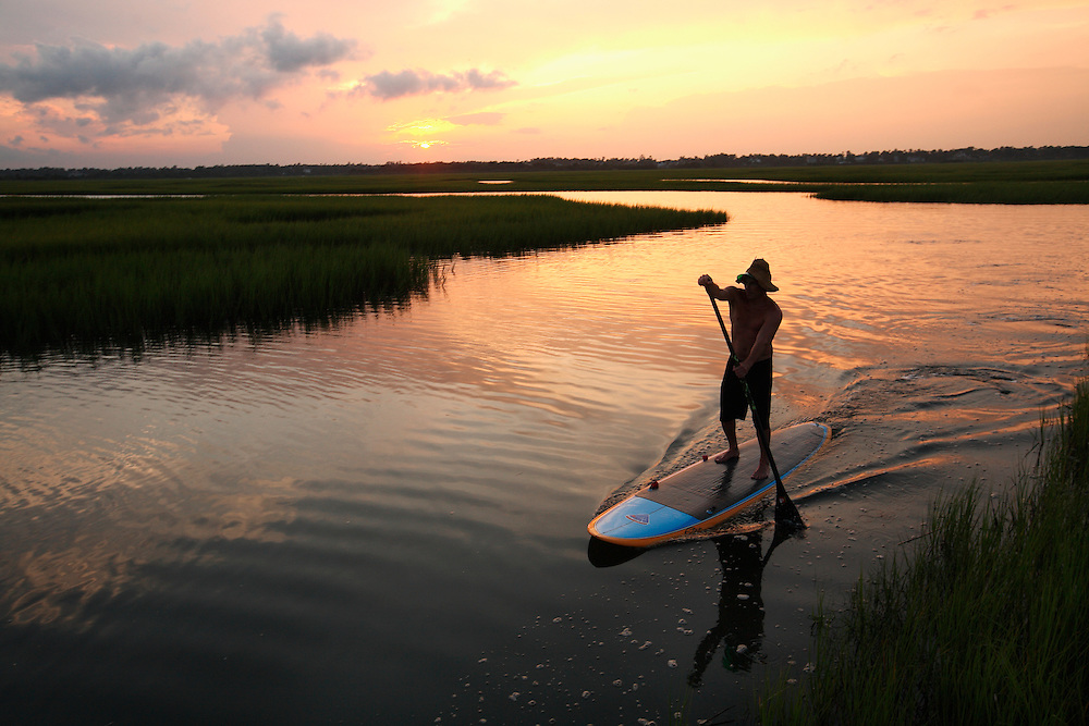 Ryan McInnis stand up paddleboarding in the Marsh at Wrightsville Beach at sunset.
