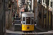 The funicular tram makes its way up the steep gradient of Rua de Bica de Duarte Belo (Elevador da Bica) in Bairro Alto, Lisbon, Portugal.