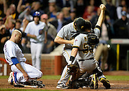 Relief pitcher Jason Grilli #39 of the Pittsburgh Pirates (C) and catcher Russell Martin #55 celebrate after Martin tagged Nate Schierholtz #19 of the Chicago Cubs out at home plate for the final out when he tried to score on a single hit by Ryan Sweeney #6 during the ninth inning at Wrigley Field on September 23, 2013 in Chicago, Illinois. The Pirates defeated the Cubs 2-1 and, with their win and a Washington Nationals loss to the St. Louis Cardinals, clinched their first playoff berth in 21 years.  (Getty Images)