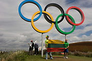 Lithuanian spectators pose for family photos beneath giant Olympic rings located on a hill in the Olympic Park during the London 2012 Olympics. This land was transformed to become a 2.5 Sq Km sporting complex, once industrial businesses and now the venue of eight venues including the main arena, Aquatics Centre and Velodrome plus the athletes' Olympic Village. After the Olympics, the park is to be known as Queen Elizabeth Olympic Park.