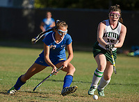Gilford's Laurel Gingrich and Newfound's Kaylan Santamaria charge the ball during NHIAA Division III field hockey on Thursday afternoon.  (Karen Bobotas/for the Laconia Daily Sun)