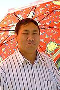 Handsome Hmong man enjoying festivities under colorful sun umbrella. Hmong Sports Festival McMurray Field St Paul Minnesota USA