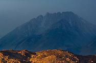 Sunrise light on hills below Basin Mountain shrouded in storm clouds, Eastern Sierra, California