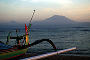 Bali's sacred mountain, Gunung Agung, viewed from Sanur beach at sunrise, with traditional Balinese outrigger canoe, a jukung, in foreground. Sanur, Bali, Indonesia.