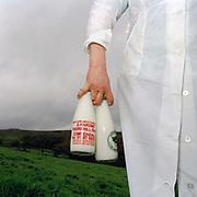 Brenda Harding, a North York Moors hill farmer holds 2 glass bottles of milk, Castleton, North Yorkshire, UK