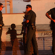 United States Border Patrol agents speak with a man and his son through the border fence at Friendship Park in San Diego, CA.