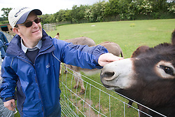 Man with learning disabilities on a trip to an animal centre feeding a donkey,