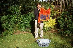 Man hanging out washing in garden,