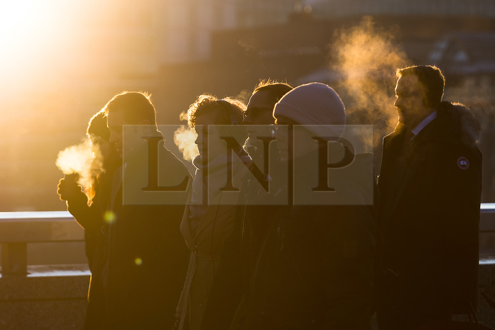 © Licensed to London News Pictures. 31/01/2019. London, UK.  Commuters walk to work across London Bridge during cold and freezing weather this morning after temperatures fell to below zero degrees in the capital last night.  Photo credit: Vickie Flores/LNP