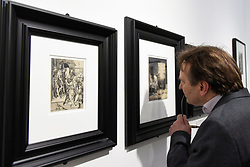 "© Licensed to London News Pictures. 03/05/2017. London, UK. A visitor studies an etching and drypoint called ""A Scholar in his study"", c1652, by Rembrandt Harmenszoon Van Rijn at the preview of the 32nd London Original Print Fair at the Royal Academy of Arts in Piccadilly.  51 international specialist dealers are presenting works in the print medium to buyers from 4 May to 7 May. Photo credit : Stephen Chung/LNP"