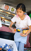 Young Hmong girl fills cooler with Asian M-150 Energy drink at family outside cafe. Hmong Sports Festival St Paul Minnesota USA