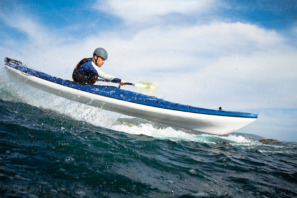 A man launches his Delta sea kayak airborne over a wave.