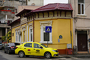 yellow taxi cab in front of a dilapidated building deterioration, Bucharest Romania