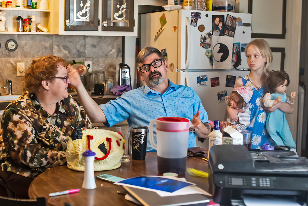 Penny Aucoin, Carl George, and their daughter Skyler in their home across from the WPX Energy site in Otis, New Mexico.