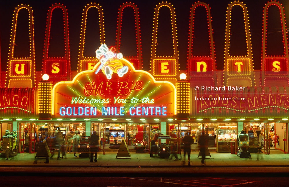 It is night-time on Blackpool's Golden Mile, the seaside resort in Lancashire, England. Like an English Las Vegas the neon lights glow to entice the holidaymaker inside where slot machines, games and rides await visitors to lose their vacation money. The Golden Mile is the name given to the stretch of Promenade between the North and South piers. It emerged in the late 19th Century, when small-time fairground operators, fortune-tellers, phrenologists and oyster bars set up in the front gardens of boarding houses, This northern seaside resort in the north-west of England is diverse in its transient holiday population whose behaviour can be routinely odd. Blackpool is the largest resort in the north of England and visited traditionally by working people from industrial towns and cities during the industrial revolution.