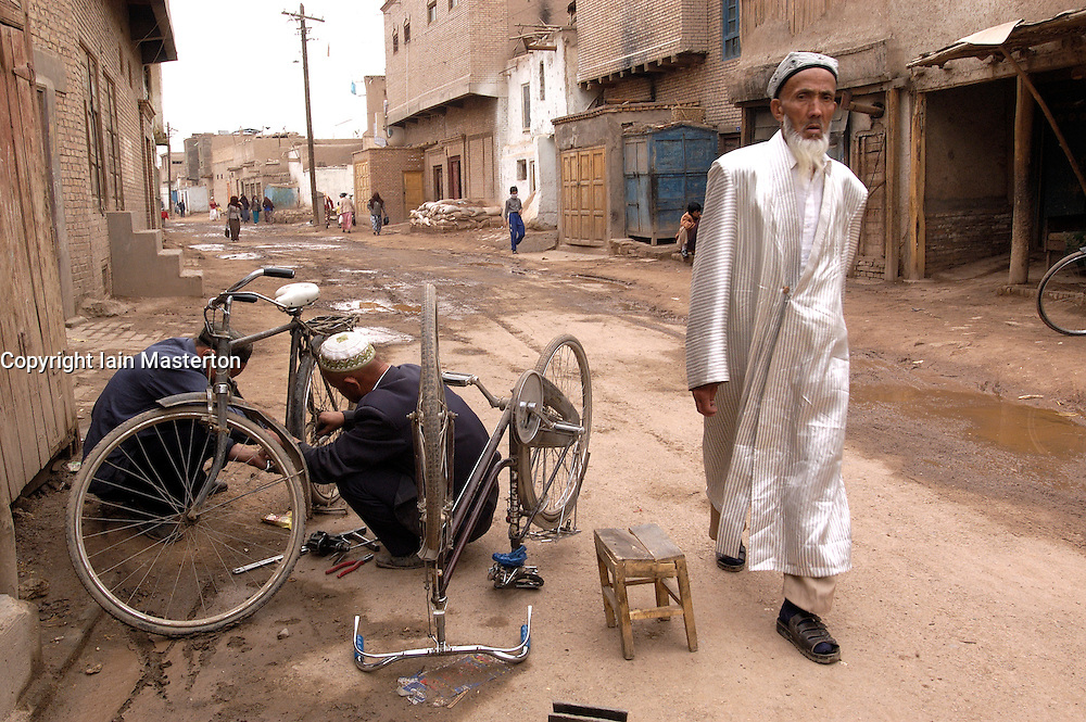 Muslim Uyghur man in traditional clothes walking in old town of Kashgar in Xinjiang China