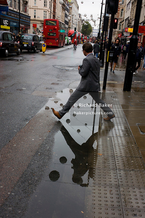 A man steps over a puddle after rainfall in Oxford Street, central London.