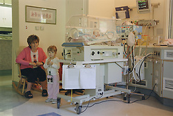 Mother and sister next to baby being ventilated in an incubator on Neonatal unit,