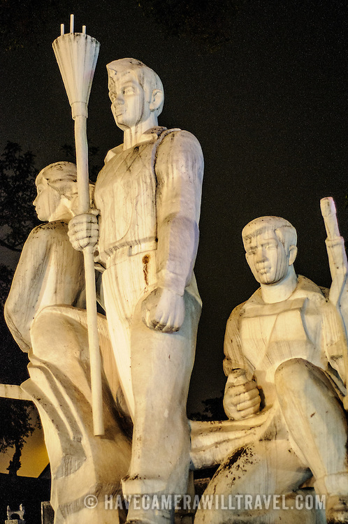 A communist statue of a worker, solider, and peasant in Hanoi's Old Quarter at night.