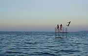Man jumps into the water from a platform