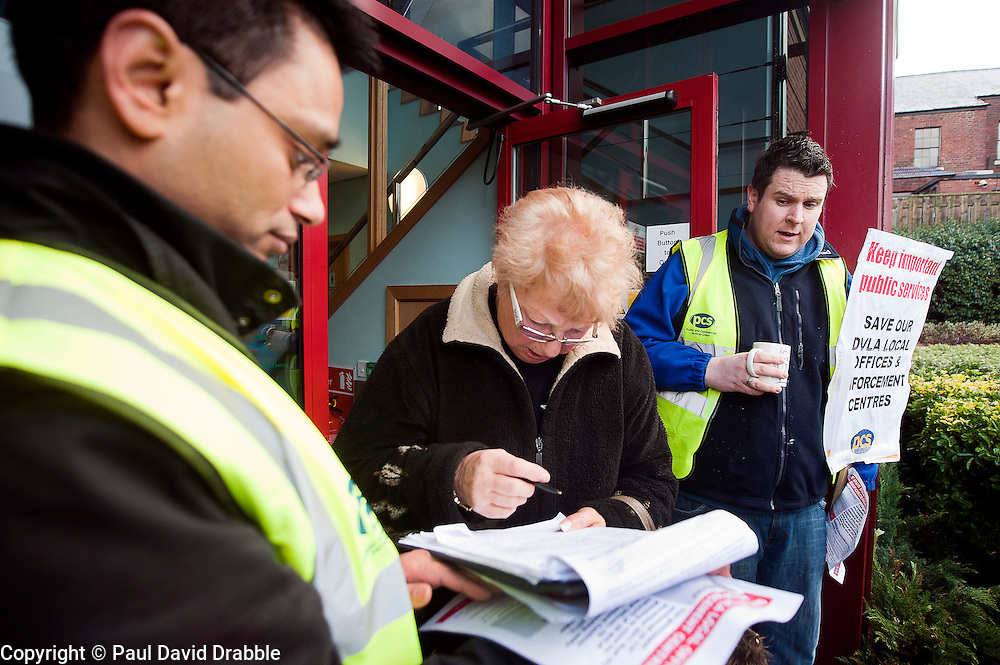 PCS members and supporters in Sheffield stage an eight-hour demonstration to protest  against the planned closure of the local office of the Driver and Vehicle Licensing Agency (DVLA). The protest was called to coincide with a visit to the premises by transport minister Mike Penning.on Monday (23 January) but according to Mike Mackie, assistant secretary of the PCS northern branch for the DVLA, the visit was canceled within 15 minutes of the Sheffield Demo being announced on the PCS website..Shajahan Miah collect a signature on the petition from a Local Office Customer with Mike Mackie.www.pauldaviddrabble.co.uk..23 January 2012 -  Image © Paul David Drabble