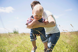Happy man playing with his son in the countryside, Bavaria, Germany