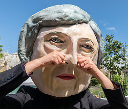 June 9, 2017 - London, London, UK - London, UK. A campaigner from the organisation Avaaz pretends to wipe away tears while wearing a Theresa May head in Westminster. Prime Minister Theresa May failed to secure a parliamentary majority in the 8 June 2017 General Election, which she claimed was needed for effective negotiations for Britain's exit from the European Union. (Credit Image: © Rob Pinney/London News Pictures via ZUMA Wire)