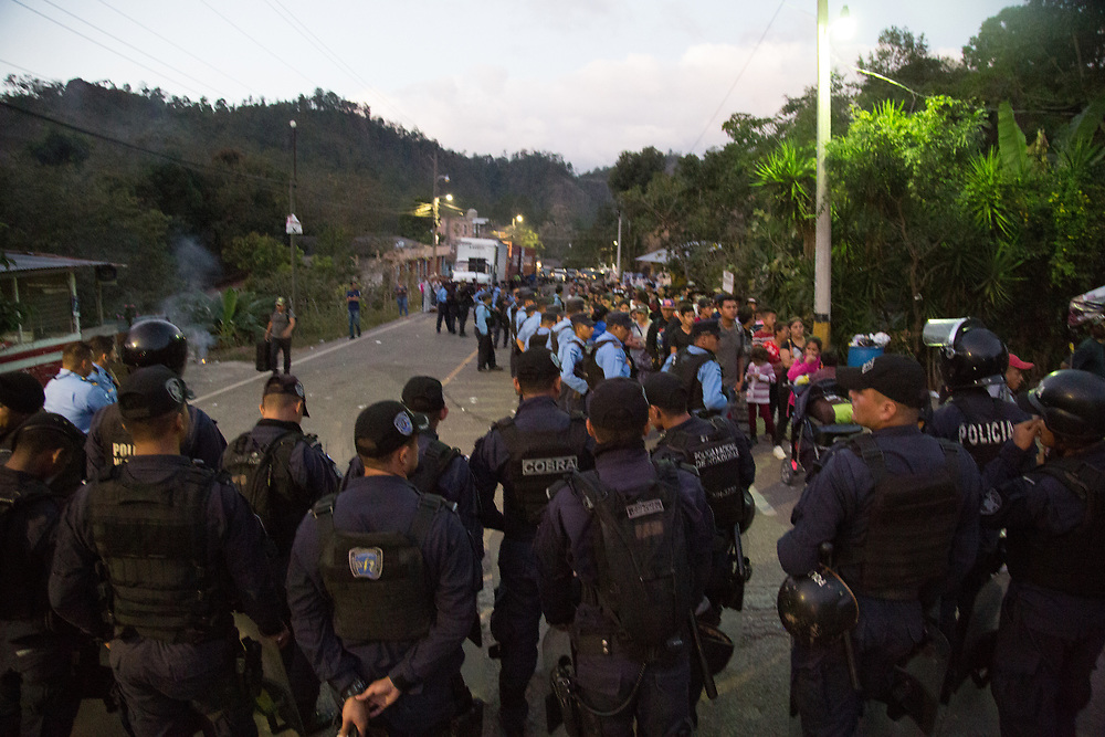 Honduran police and special forces keep a line of migrants under control, funneling them into an administrative area where their documents were checked. Anyone under 21 travelling without their parents or the legal permission of both their parents was returned by bus to San Pedro Sula.