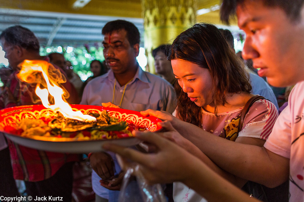 "15 SEPTEMBER 2013 - BANGKOK, THAILAND: Hindus in Bangkok pray on the last day of Ganesha Chaturthi celebrations at Shiva Temple in Bangkok. Ganesha Chaturthi is the Hindu festival celebrated on the day of the re-birth of Lord Ganesha, the son of Shiva and Parvati. The festival, also known as Ganeshotsav (""Festival of Ganesha"") is observed in the Hindu calendar month of Bhaadrapada. The festival lasts for 10 days, ending on Anant Chaturdashi. Ganesha is a widely worshipped Hindu deity and is revered by many Thai Buddhists. Ganesha is widely revered as the remover of obstacles, the patron of arts and sciences and the deva of intellect and wisdom. The last day of the festival is marked by the immersion of the deity, which symbolizes the cycle of creation and dissolution in nature. In Bangkok, the deity (statue) was submerged in the Chao Phraya River.     PHOTO BY JACK KURTZ"