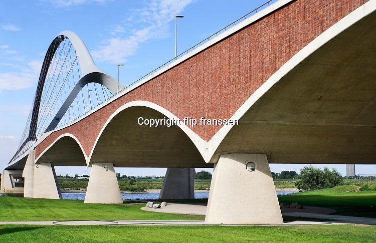 Nederland, Nijmegen, 19-7-2020  De nieuwe stadsbrug van de stad Nijmegen, de Oversteek . De brug is vernoemd naar de heldhaftige oversteek van de rivier de Waal die Amerikaanse soldaten op dit punt maakten tijdens de operatie Market Garden in de tweede wereldoorlog om met succes de oude Waalbrug te veroveren. De stalen overspanning is een belangrijke schakel in de ontlasting van de stad van het doorgaande verkeer De Oversteek is een boogbrug van 285 meter lang en 60 meter hoog en is de op een na langste hoofd overspanning van Nederland, en de grootste boogbrug van Europa met een enkelvoudige boog. Architecten Poulissen en Ney . De brug wordt 23 november in gebruik genomen. De nieuwe oeververbinding moet zorgen voor een betere spreiding en doorstroming van verkeer binnen de stad Nijmegen. Na 75 jaar is er eindelijk een tweede vaste verbinding voor de stad. De oude waalbrug krijgt vanaf eind dit jaar groot onderhoud, waarna de volle capaciteit van beide bruggen pas gebruikt kan worden. De skyline van de stad is veranderd. Foto: ANP/ Hollandse Hoogte/ Flip Franssen