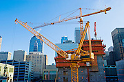 High-rise construction cranes add to an urban skyline on a sunny day.
