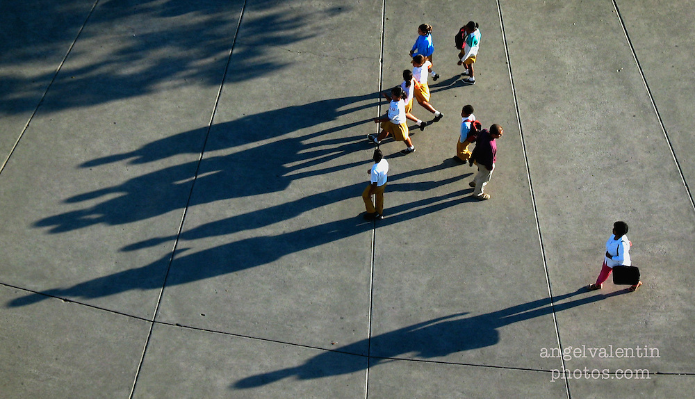 1/29/03---photo by A.Enrique Valentin---<br /> cuba29e----<br /> School children cast long shadows as they walk on the plaza in the twon square on a recent morning  in Santa Clara in the province of Villa Clara.