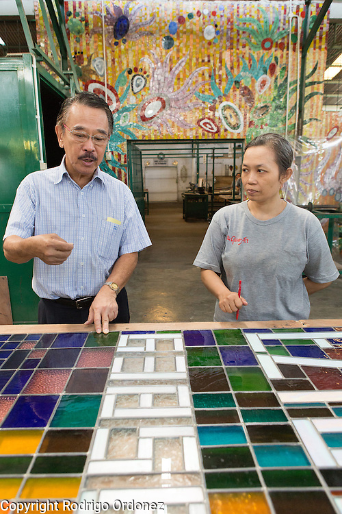 Eztu Glass founder and CEO Brian Yaputra (left) talks to an employee about a stained glass window at his company's factory in Tangerang, near Jakarta, Indonesia, on July 2, 2015.
