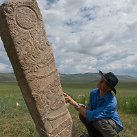 "Mongolian archaeologist Tovuudorj Sanjmyatov (""Sasha"") (MR) sketches carvings on a 2700+ year-old, bronze age deer stone monument at Ulaan Tolgoi archaeological site near Lake Erkhel, north of Muren, Mongolia."