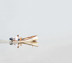 A man steering a small dinghy on a placid Blackwater River in Essex.