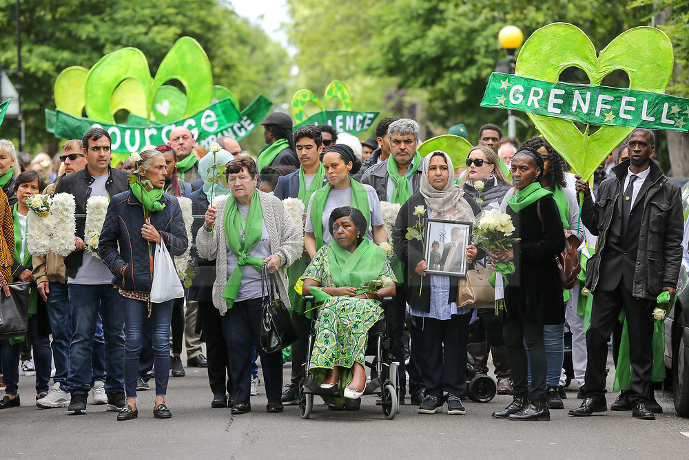 © Licensed to London News Pictures. 14/06/2019. London, UK.  Survivors, family and friends of the victims wear symbolic green scarf take part in a silent procession marching from St Helen's Church to Grenfell Tower to commemorate the second anniversary of the Grenfell Tower fire. On 14 June 2017, just before 1:00 am a fire broke out in the kitchen of the fourth floor flat at the 24-storey residential tower block in North Kensington, West London, which took the lives of 72 people. More than 70 others were injured and 223 people escaped. Photo credit: Dinendra Haria/LNP