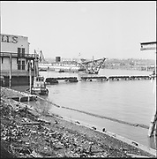 """9904-B02-8. """"Dredge pipe & pontoons holding up electric cable at Crown Mills, March 26, 1957"""" caption published in the Oregonian March 26, 1957 pg. 15. """"Tug Plucks Power Cables to aid River Dredging."""" (Cable went from Crown Mills to the Permanente Cement plant. 120mm negatives. View looking west, showing the east bank of the Willamette River.)"""
