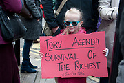 Tens of thousands of health workers, activists and members of the public protested against austerity and cuts in the NHS National Health Service on March 4th 2017 in London, United Kingdom. A young girl wearing sunglasses holds a placard saying Tory Agenda. Survival of the richest. Hashtag Save OurNHS.