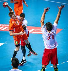 The Dutch handball player Niels Versteijnen and Mehmet Demirezen, Doruk Pehlivan in action during the European Championship qualifying match against Turkey in the Topsport Center Almere.