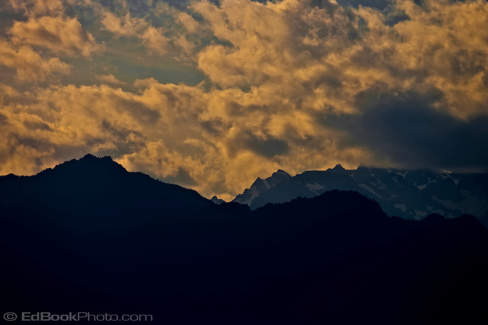 Mount Jupiter and Mount Constance display rugged dark silhouettes against an alpenglow lit sky with warm colored clouds brusing Mt Constance.