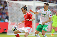 Gareth Bale of Wales shields the ball from Craig Cathcart of Northern Ireland.UEFA Euro 2016, last 16 , Wales v Northern Ireland at the Parc des Princes in Paris, France on Saturday 25th June 2016, pic by  Andrew Orchard, Andrew Orchard sports photography.