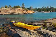 Kayak on Precambrian shield rock along shoreline of Georgian Bay<br />near Snug Harbour<br />Ontario<br />Canada