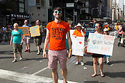 """A man wears a t-shirt reading """"Turkey baster baby"""" as he walks with a group of children of same-sex parents."""